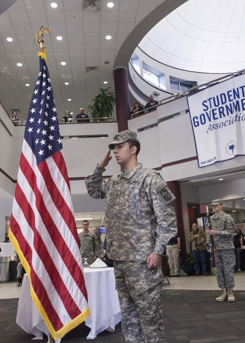 Student saluting flag at Veterans Day event