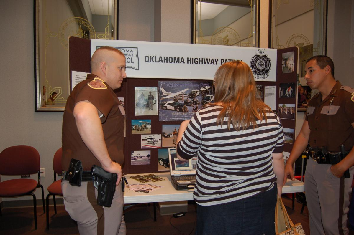 Oklahoma Highway patrol officer speaks with students at career fair.